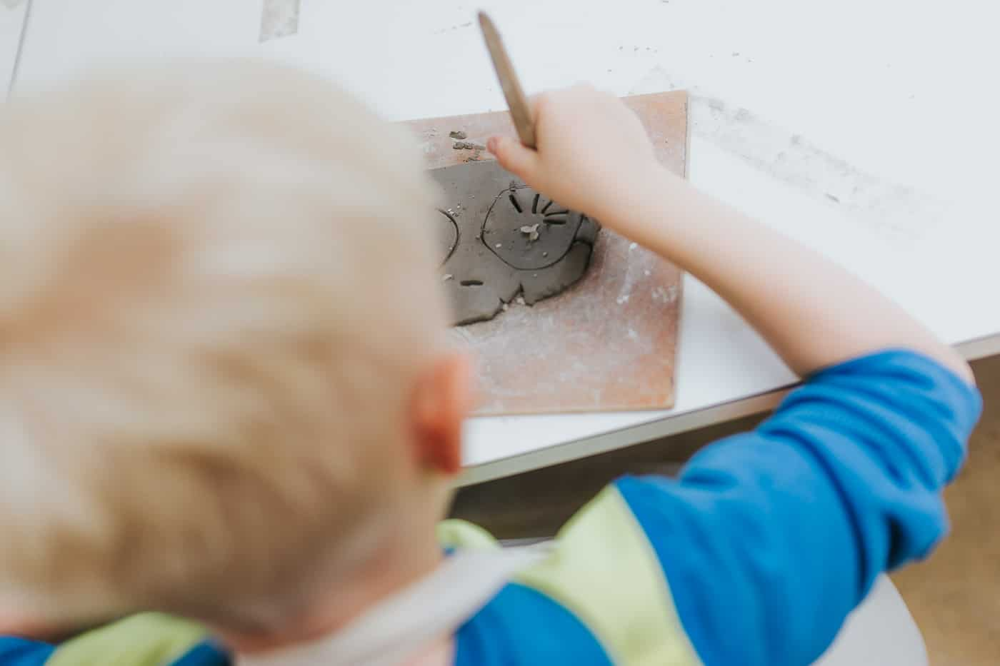 A boy etching into his clay creation