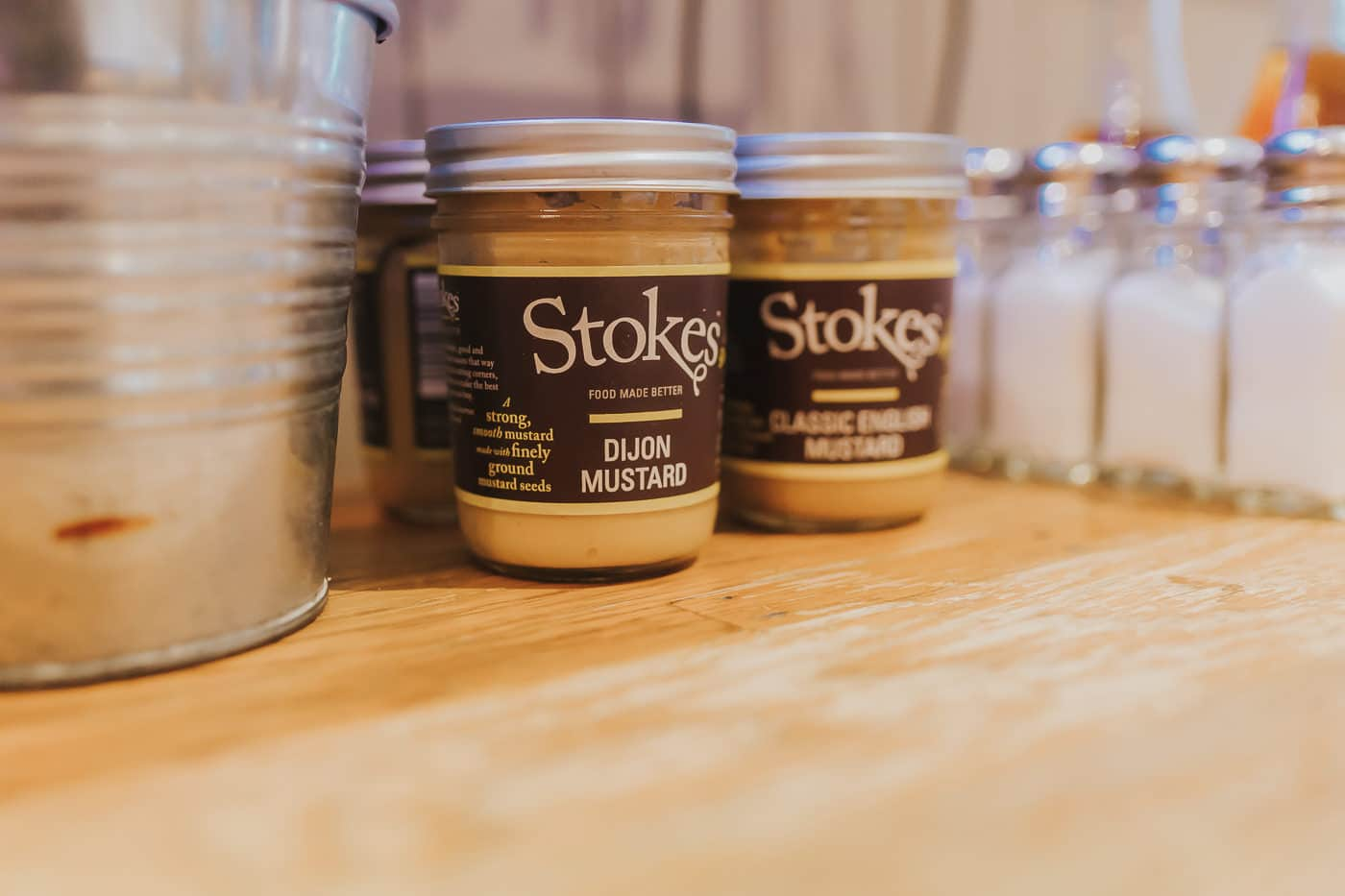 Two jars of mustard on a wooden table