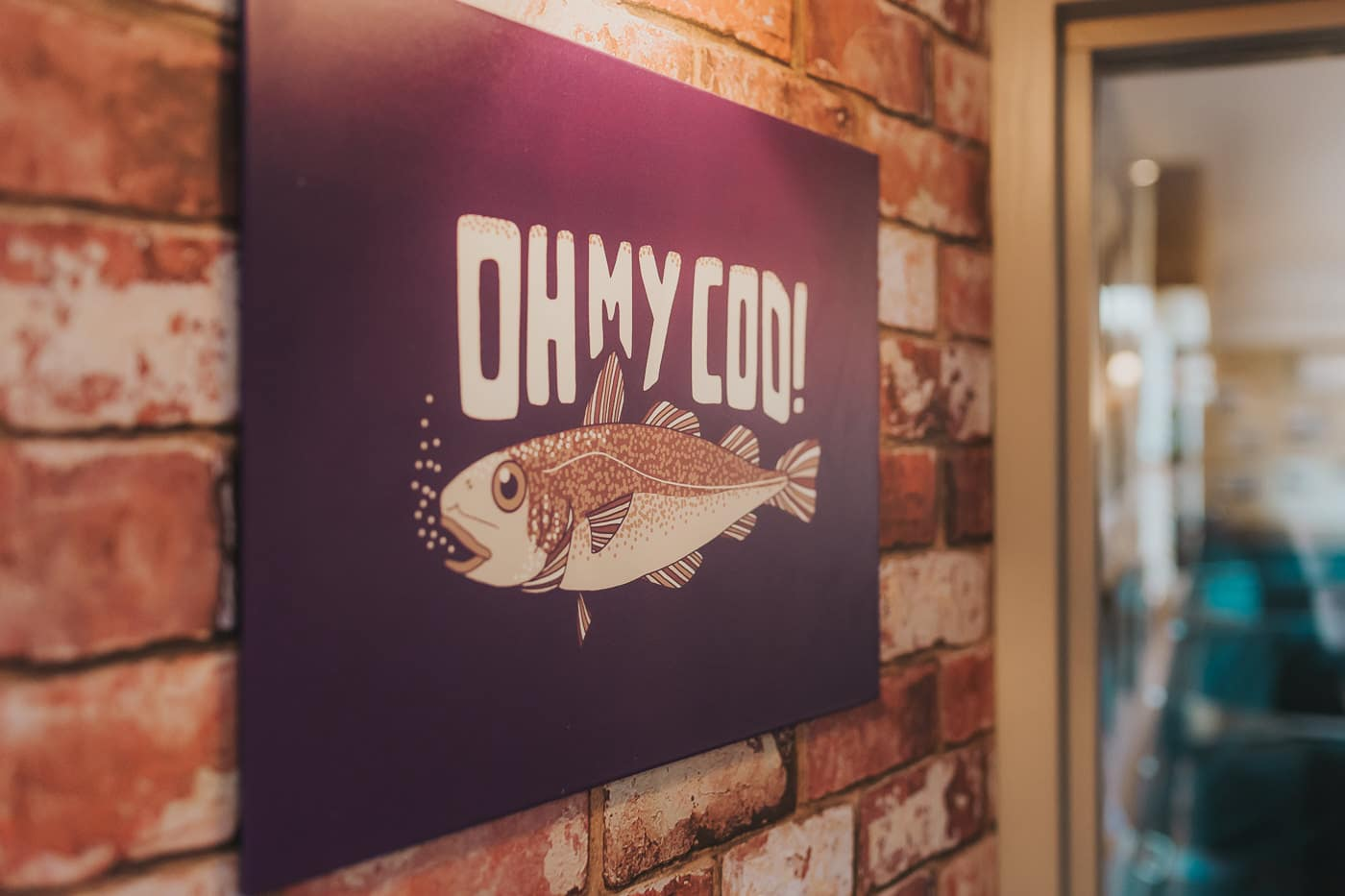 Sign in a fish and chip shop which says 'oh my cod'