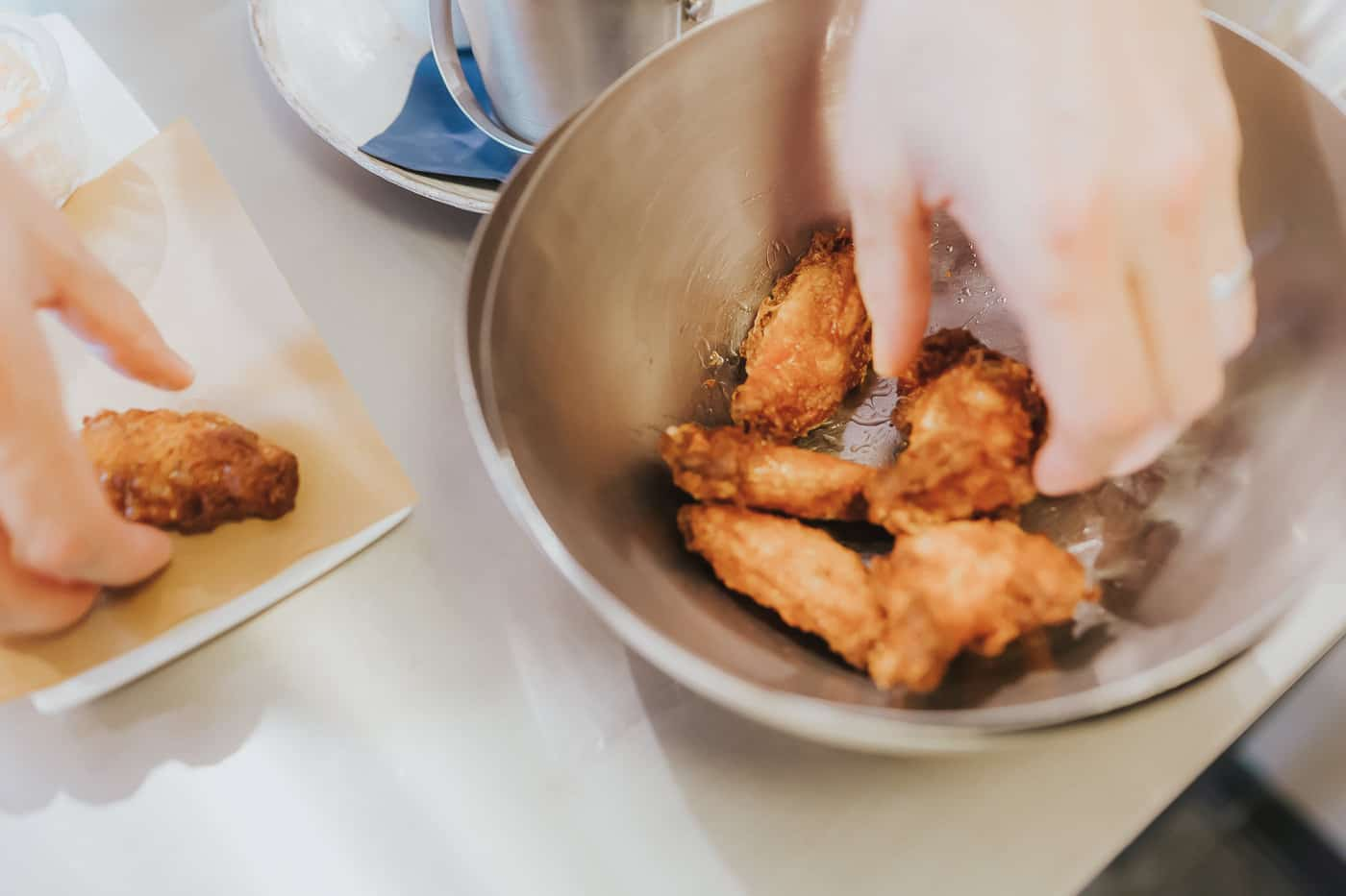 Deep fried chicken wings being seasoned and served onto a plate