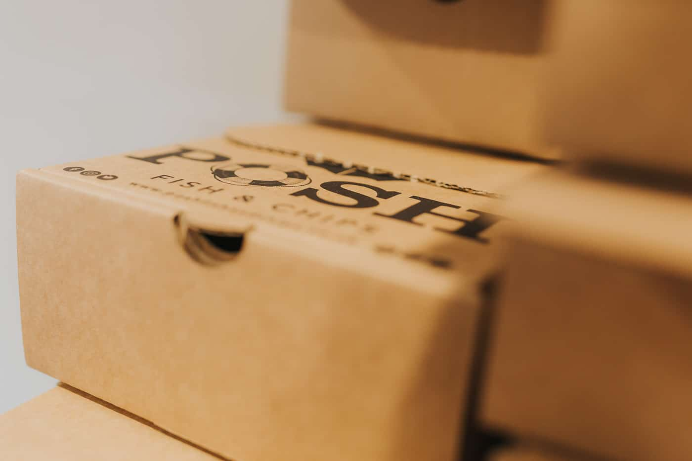 Close up of a takeaway box with the 'posh fish and chips' logo on