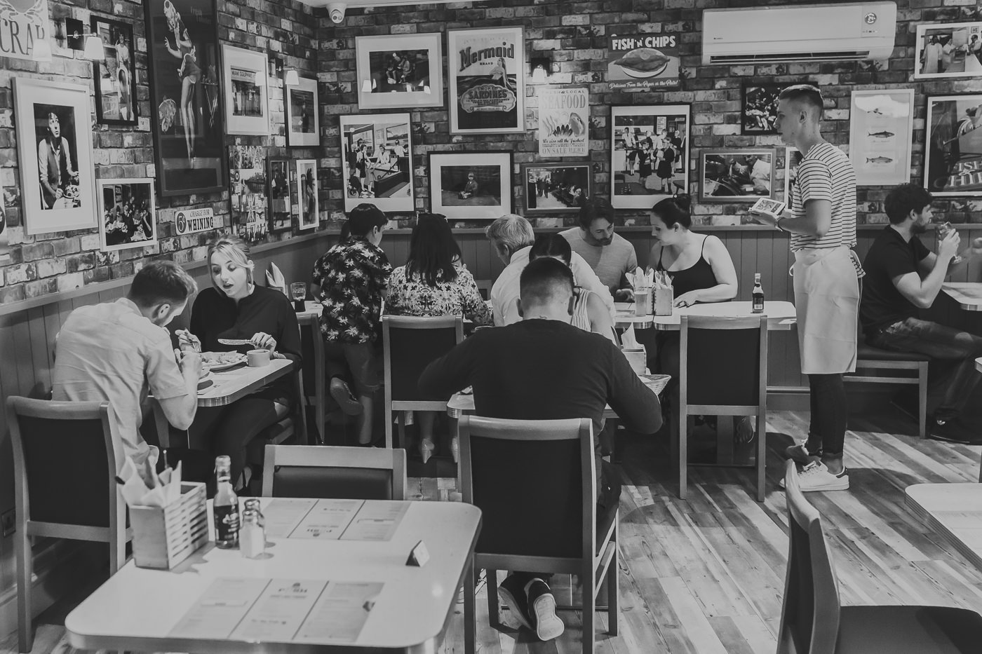 Black and white image of people sitting in a restaurant