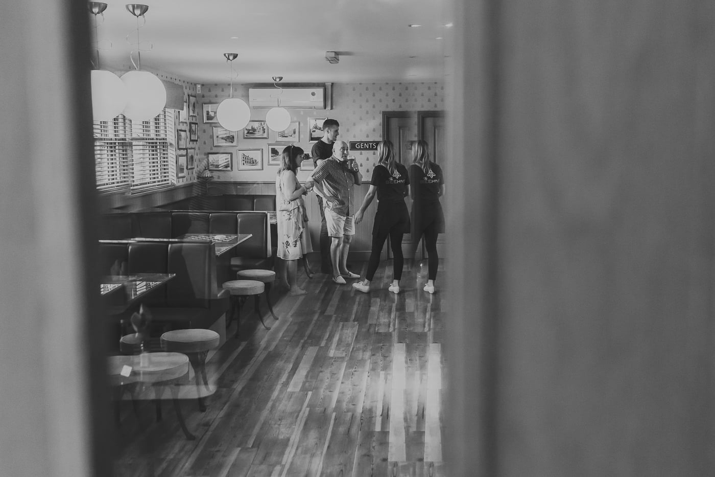 Candid shot of people looking around a pub in black and white