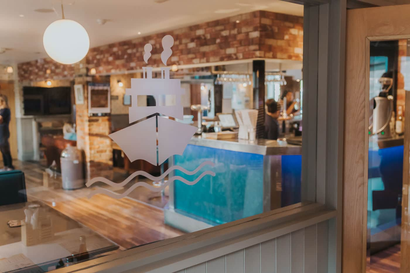 Logo of a fish and chip restaurant etched onto a window with a bar behind it