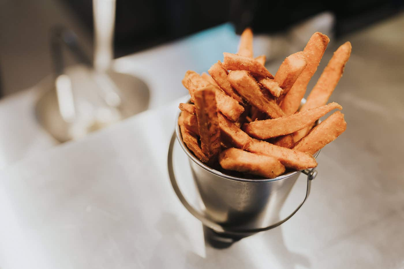 Portion of sweet potato fries on a serving pass ready to go out