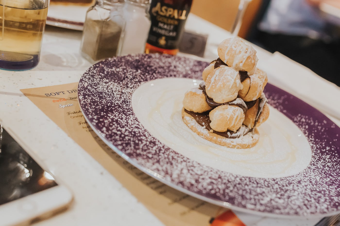 A stack of profiteroles on a plate with chocolate sauce and icing sugar
