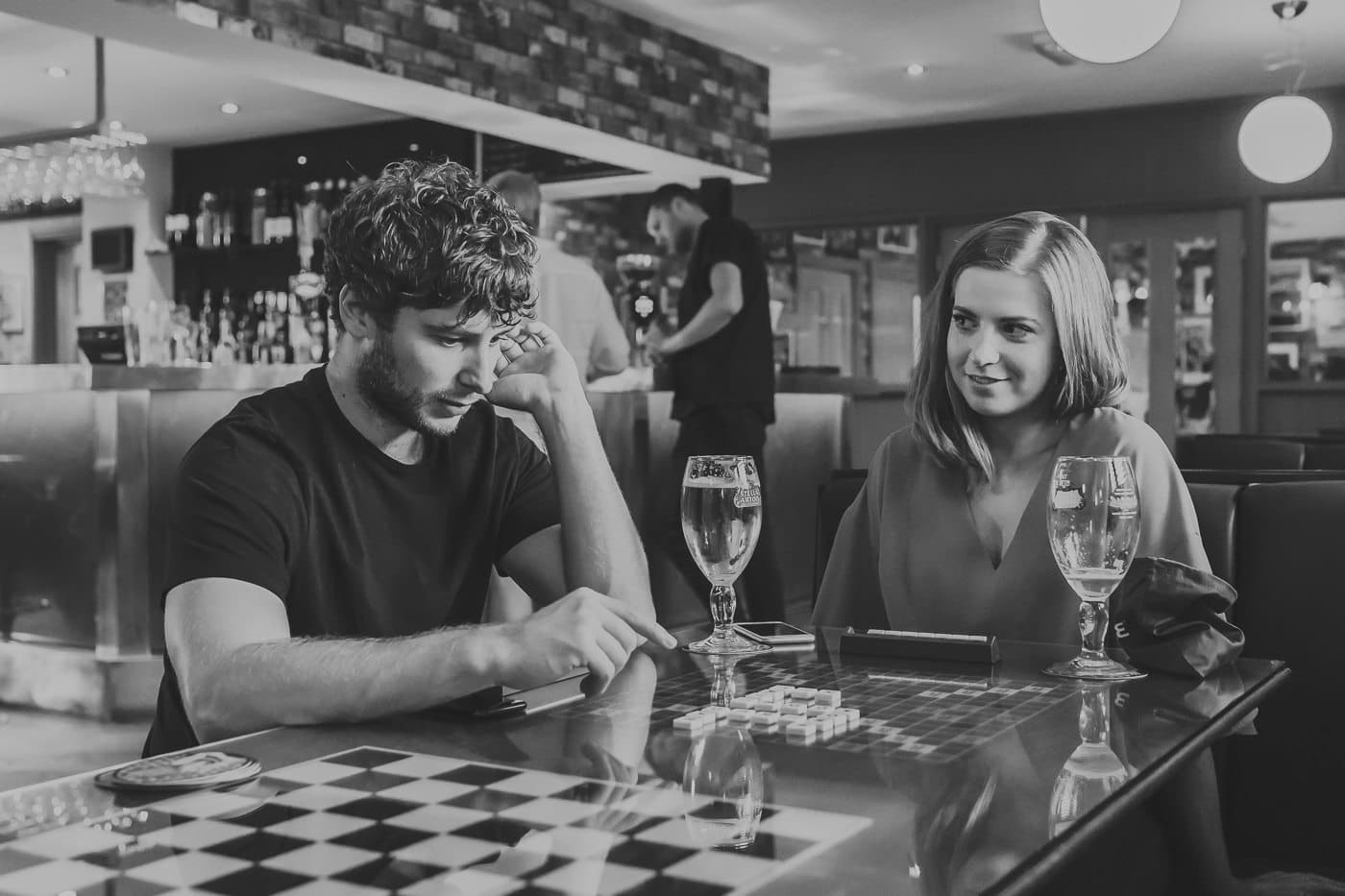 Two people sat at a table playing scrabble in a pub also drinking wine