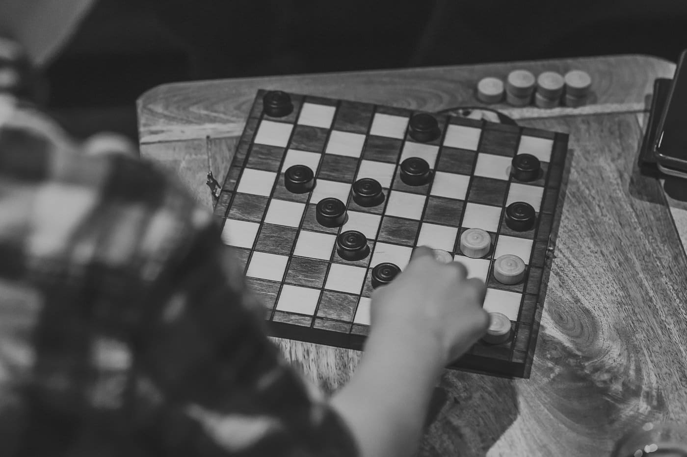 Black and white image of a father and son playing draughts