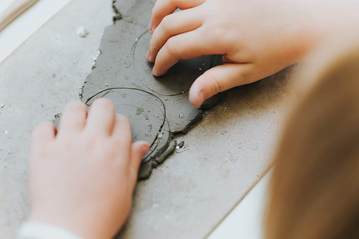 A girl marking out clay to cut it