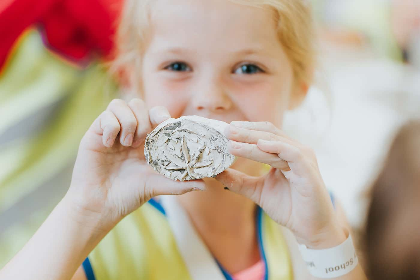 A girl holding up the clay item she has made