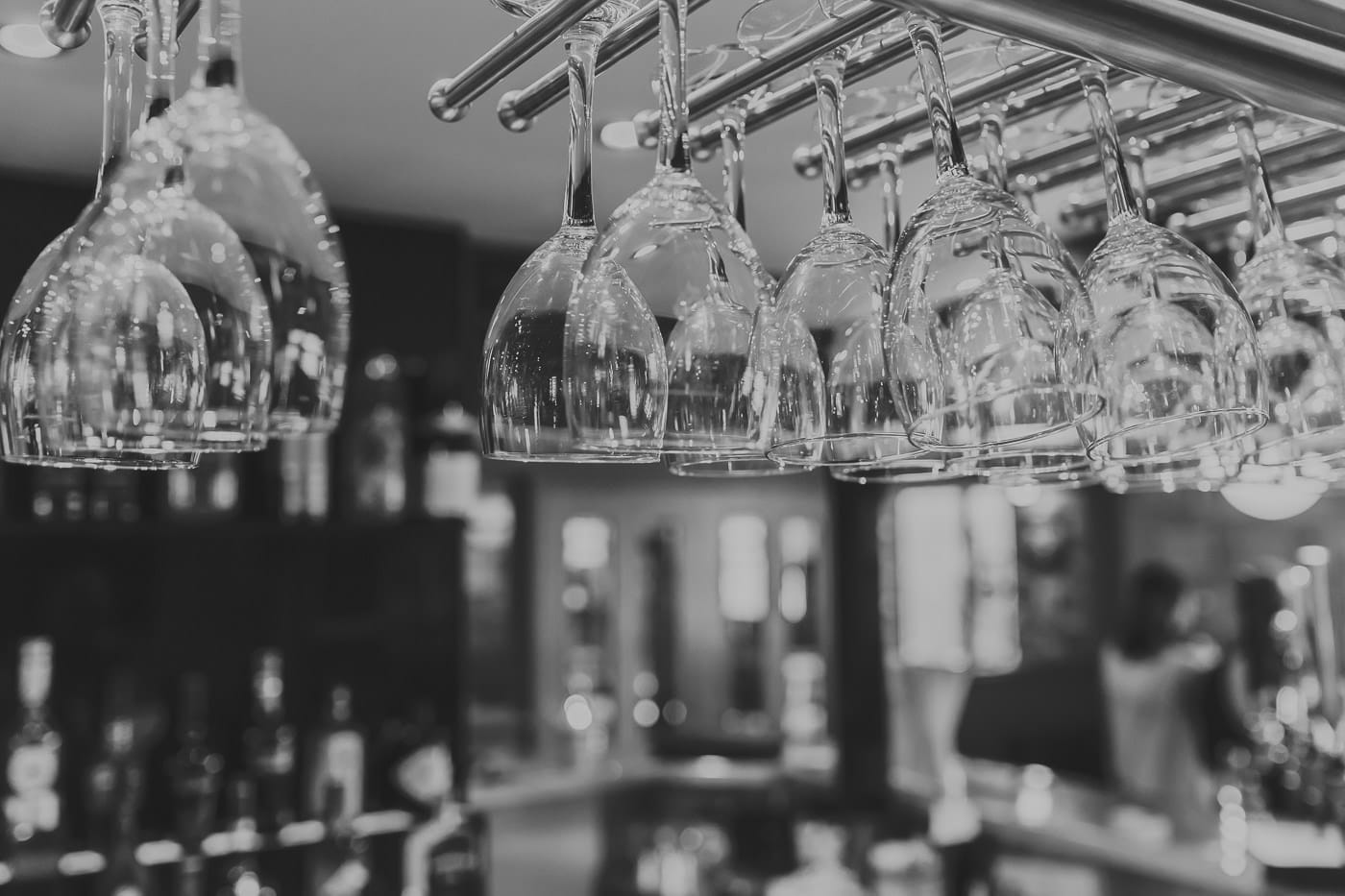 Black and white shot of wine glasses hanging above a bar