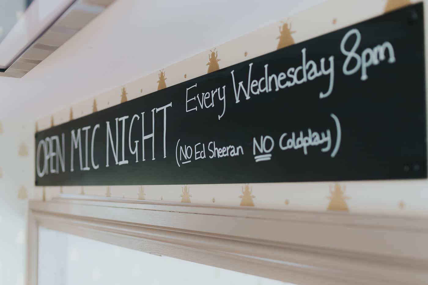 Close up of a chalk board which says 'open mic night Every Wednesday 8pm (no Ed Sheeran no Coldplay)