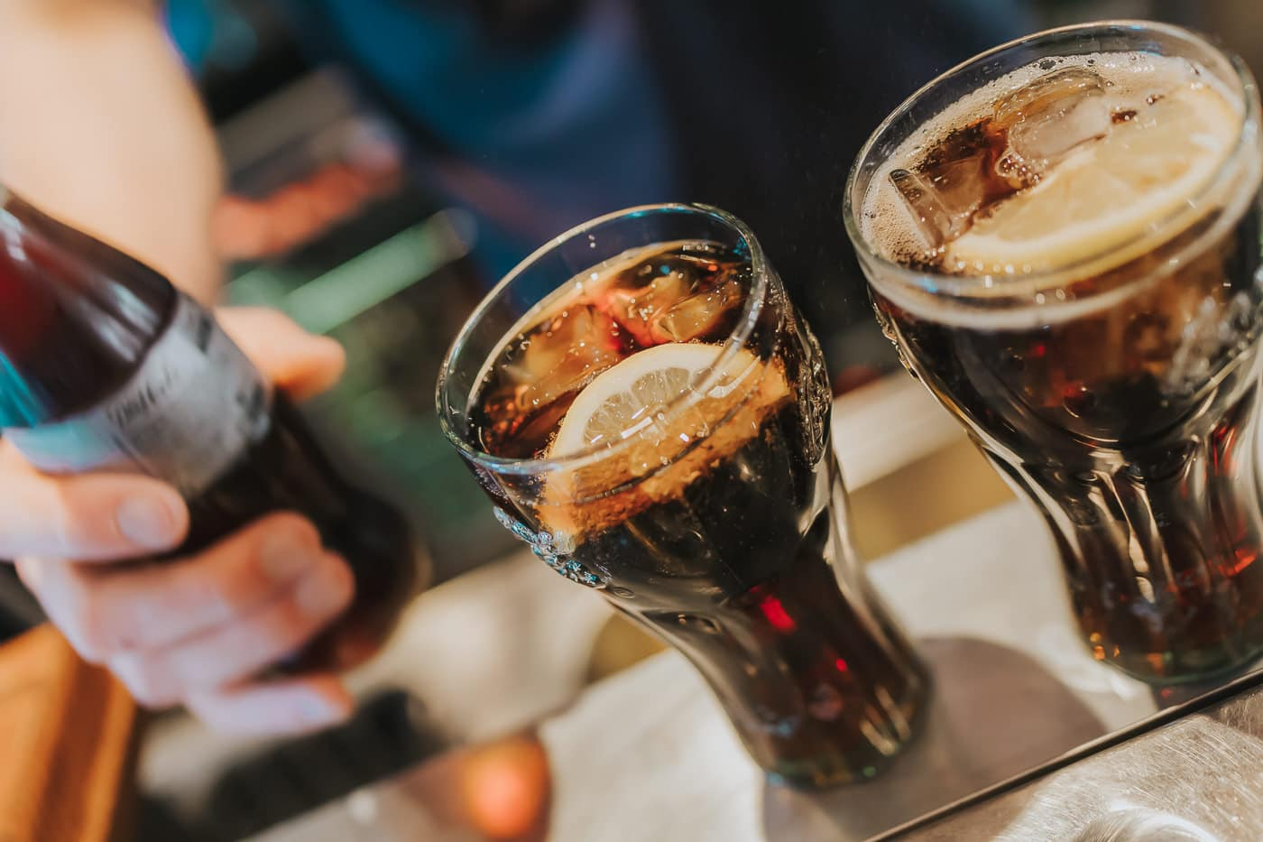 Two glasses of Coke on a bar