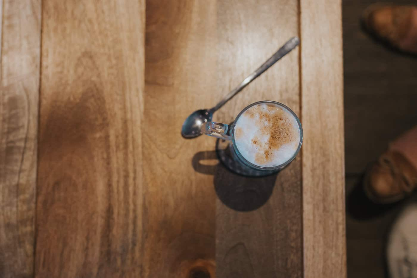 Top down view of a latte and a spoon on a wooden table