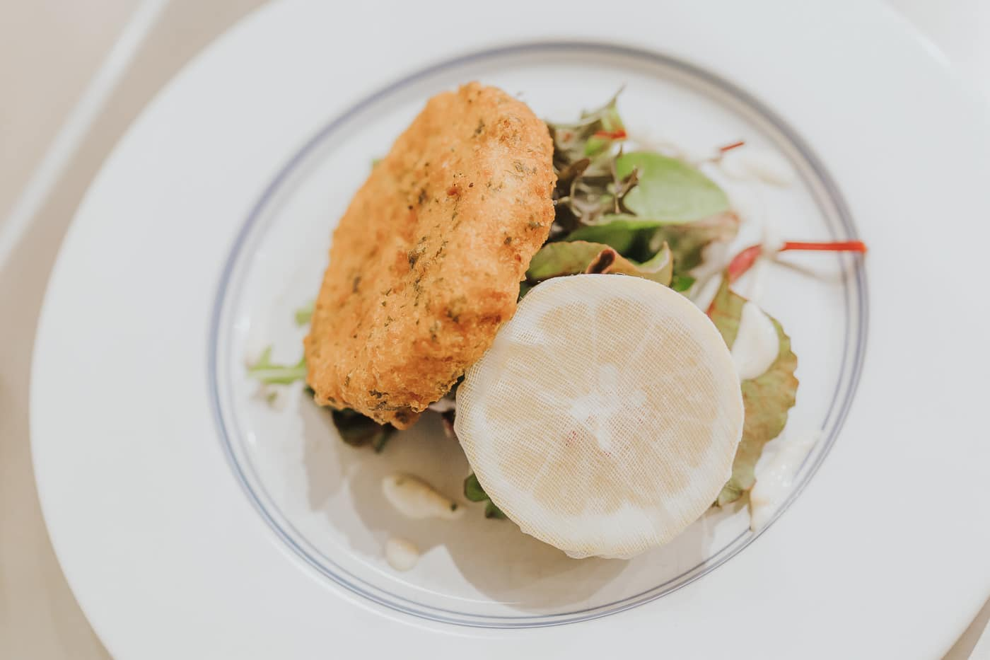 A top down view of a fishcake resting on a salad