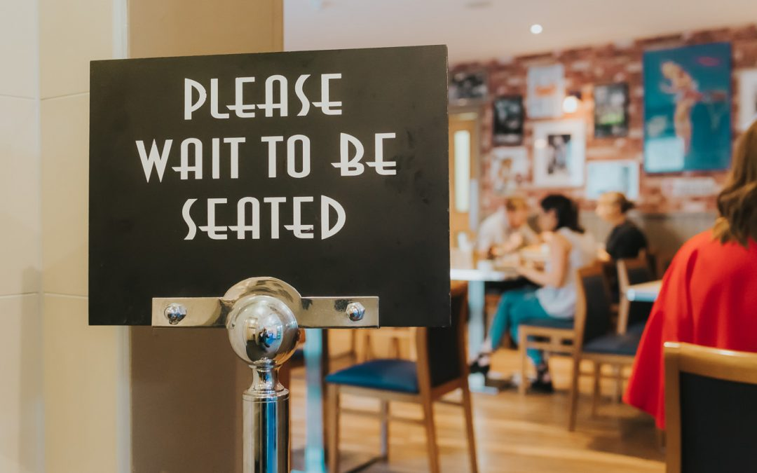 Sign which says 'please wait to be seated'
