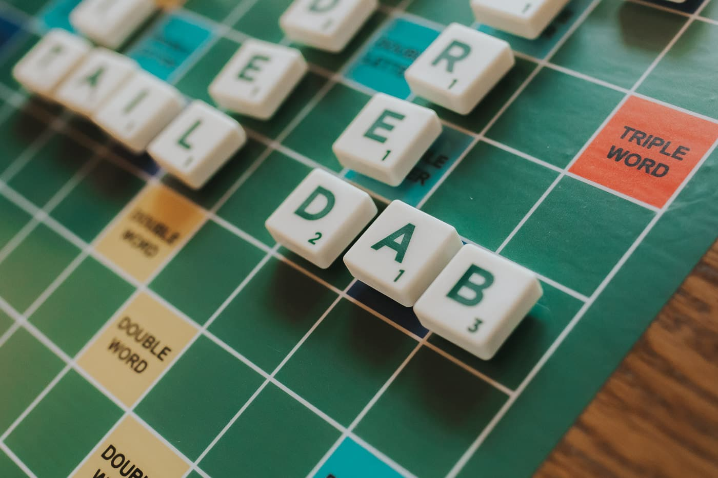 close up of a scrabble board with tiles on, the word in focus is Dab