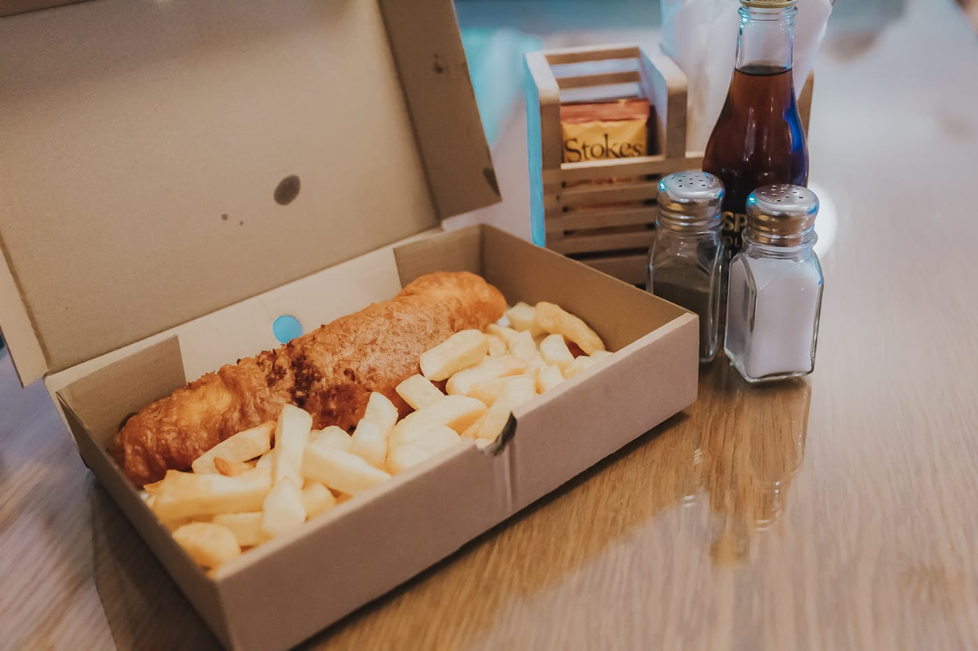 A portion of fish and chips in a takeaway box