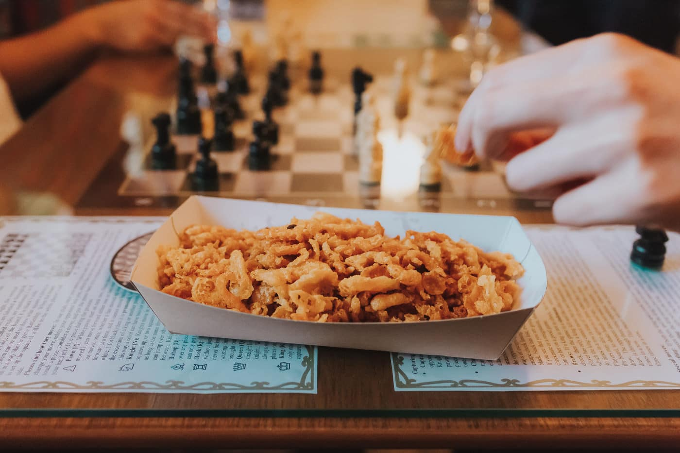 fish and chip scraps in front of a chess board
