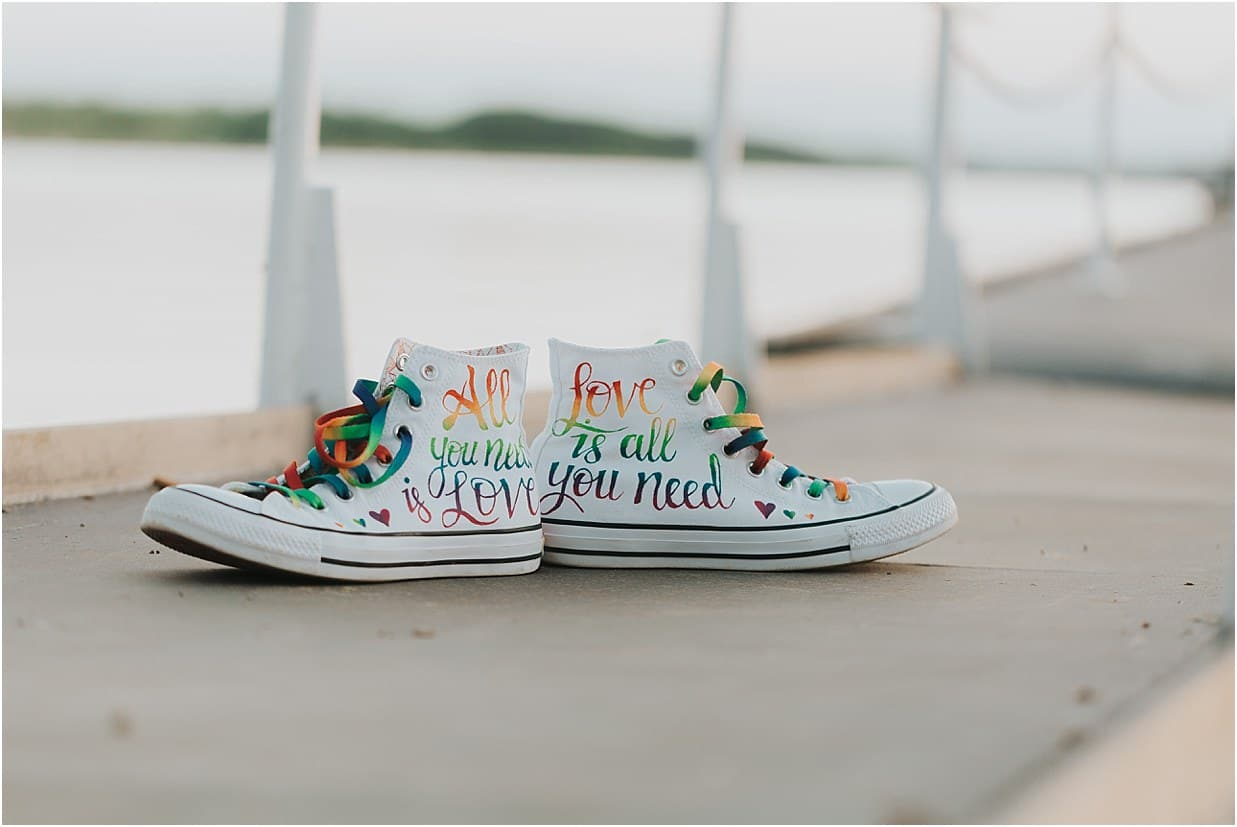 Custom pair of high top converse one says All you need is love, the other says Love is all you need