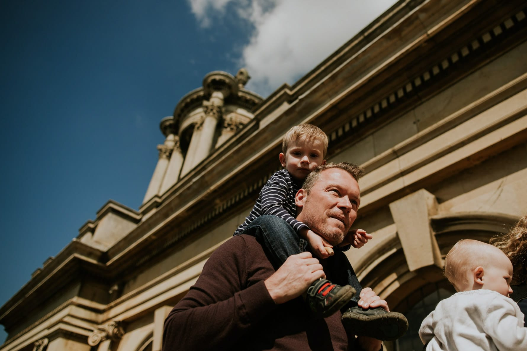 Dad carrying a boy on his shoulders next to Normanton Church